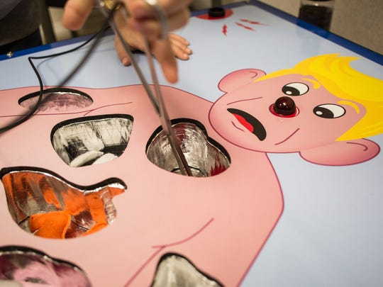 Kids play with an oversized operation game during the