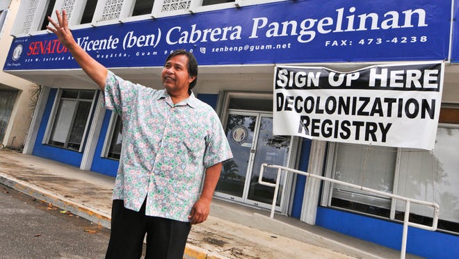 """In this file photo, the late Sen. Vicente """"Ben"""" Pangelinan waves to a passing motorist in front of his office on Nov. 22, 2011. Pangelinan spearheaded efforts to register people for the Decolonization Registry."""