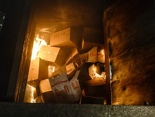 Boxes of unused drugs burn in the opening of an incinerator
