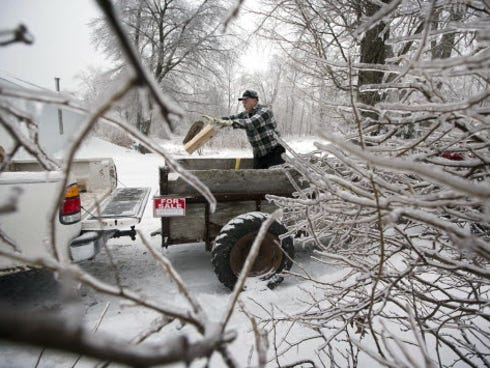 Ken Finnegan loads firewood into his truck amid tree branches coated with ice in Litchfield, Maine. State utilities had restored power to most across the state, but more snow threatened additional outages Sunday into Monday.
