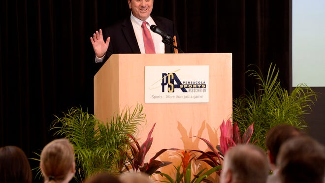 Bill Vilona, veteran sports reporter for the Pensacola News Journal, addresses the overflow crowd after being inducted into the Pensacola Sports Association Hall of Fame during the PSA COX Annual Awards Banquet at the Sanders Beach-Corinne Jones Community Center.