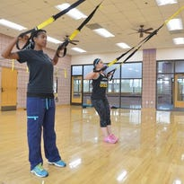 Sineyda Ortiz works with instructor Dorothy Reynolds on TRX training at the Payne Center on the University of Southern Mississippi campus.