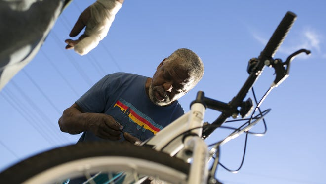 Earl Morris, a customer at the Rusty Spoke community bicycle collective, works on a bike in front of the shop on May 9, 2018, in Phoenix.