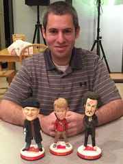 """Phil Sklar shows off the three """"Home Alone"""" bobbleheads"""