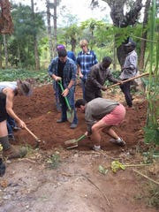 Students from UW-Stevens Point work with Kenyans to install banana circles.