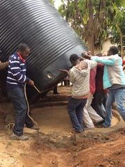 Students from UW-Stevens Point help Kenyans install a rainwater tank to collect clean water for a produce farmer.