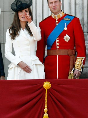 FILE - Britain's Prince William, Duke of Cambridge, right, his wife Catherine, Duchess of Cambridge, react on the balcony of Buckingham Palace after returning from the Trooping the Colour ceremony to mark the Queen's official birthday in London, in this, June 11, 2011 file photo. Among the roughly 5 million visitors expected in New York this holiday season, at least two are certain to get the royal treatment: Britain's Prince William and his wife, Kate. They're due to arrive Sunday Dec. 7, 2014 for the first trip either has made to the United States' biggest city, and William also is set to visit the nation's capital for the first time. (AP Photo/Akira Suemori, File)