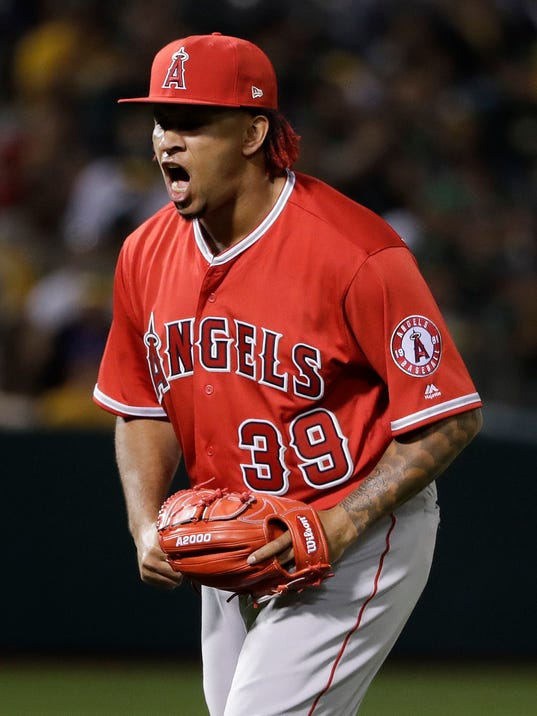 Los Angeles Angels relief pitcher Keynan Middleton (39) reacts after getting Oakland Athletics' Jed Lowrie to fly out to end the eighth inning of a baseball game Friday, March 30, 2018, in Oakland, Calif. (AP Photo/Marcio Jose Sanchez)