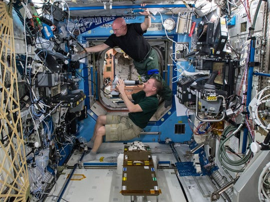 In this April 9, 2015 photo made available by NASA, astronauts Terry Virts, bottom, and Scott Kelly perform eye exams in the Destiny Laboratory of the International Space Station as part of ongoing studies on vision health in microgravity. Kelly sees his nearly completed one-year mission as a 'steppingstone' to Mars. America's record-breaking astronaut will submit to numerous tests when he returns from the International Space Station. Researchers want to see if Kelly would hit the ground running if this were Mars instead of Earth.