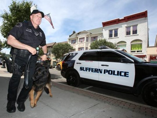 Suffern Police Officer Lou Venturini and K-9 Officer Patriot patrol Lafayette Road in the village on Thursday. The villages of Airmont and Hillburn considered dropping the town of Ramapo police department and contracting with the Suffern Police.