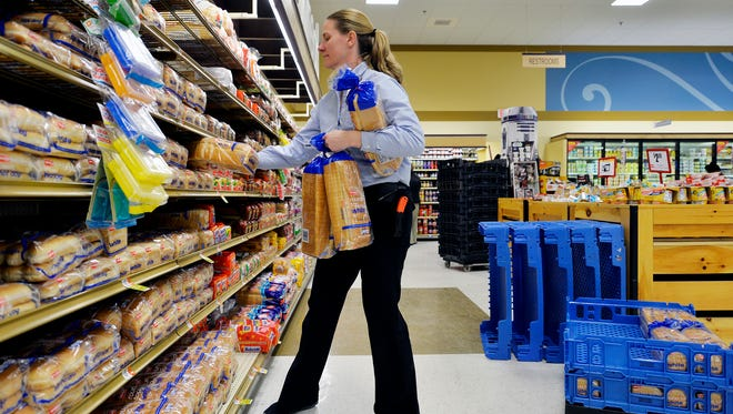 Assistant manager Brandi Cooke restocks bread at Weis Markets in York Township. Snowfall of between 1-2 feet is predicted to fall during the weekend storm.