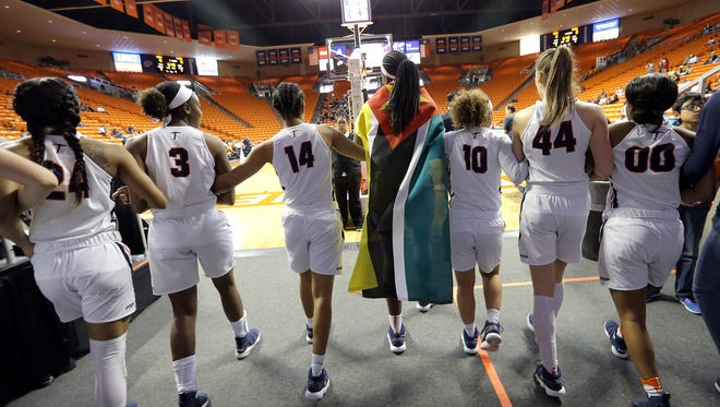 UTEP's lone senior Tamara Seda, wrapped in the flag of her home country Mozambique, leads the Miners onto the floor one last time at the Don Haskins Center.