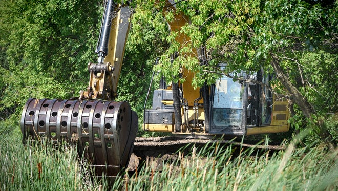 An excavator is used to remove large floating bogs Wednesday, July 11, from Linneman Lake near Avon. Crews have removed 150 truck loads of bog material from the lake so far.
