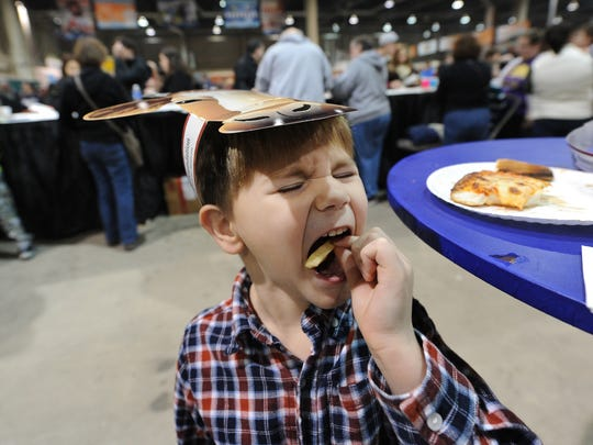 Wayne Witter, 5,  of Mechanicsburg, opens wide as he chows down on some french fries in the food court at the Pennsylvania Farm Show in Harrisburg, Pa. in 2016.