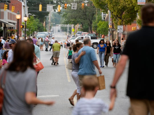 People walk up and down North Beaver Street for First Friday on Friday, Aug. 1, 2014.