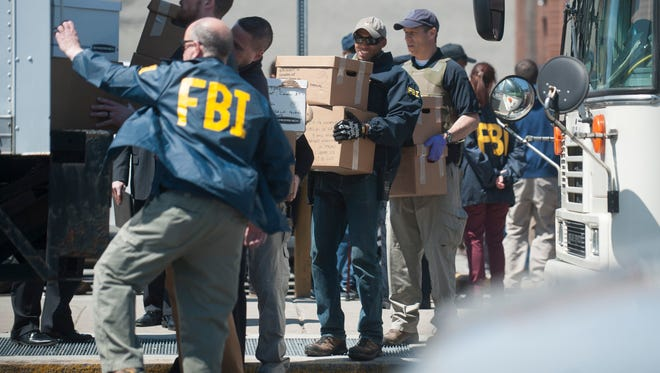 FBI agents load a truck with boxes of material removed from a methadone clinic located at 5th and Market streets in Camden on Wednesday, April 18, 2018.