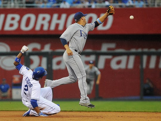 Kansas City's Alcides Escobar (2) slides safely into second base before running to third as Tampa Bay infielder Asdrubal Cabrera (13) misses the ball during a game on  July 7, 2015, at Kauffman Stadium in Kansas City, Mo.