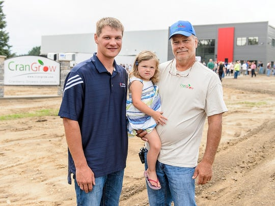 Adam Nemitz (left) is pictured with his father and daughter near the new CranGrow processing facility in Tomah, Wisconsin on Aug. 11, 2016.