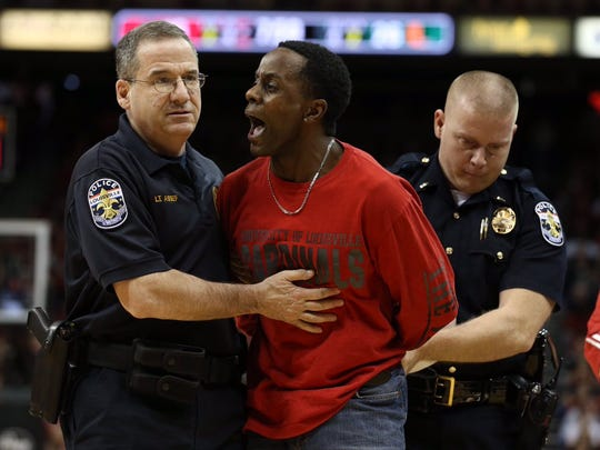 A fan was removed by police from the KFC Yum! Center court during the first half of the Louisville-Miami basketball game on Saturday, Feb. 11, 2017.