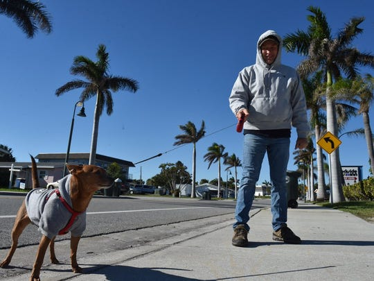 "Greg Cwik, of Fort Pierce and his dog, Rufus, brave the cold weather on a morning walk along Seaway Drive Jan. 4, 2018. ""I hate it"" Cwik said about the cold weather."