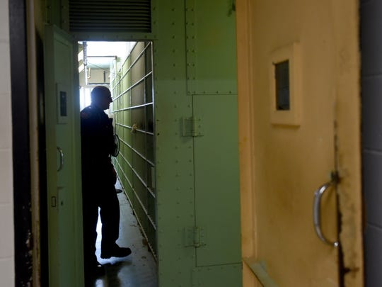 Jail Administrator Lt. Chip Udischas takes a note from an inmate in one of the cell blocks of the Coshocton Justice Center. The facility, built to house 15 of inmates, housed 75 on Sept. 15.