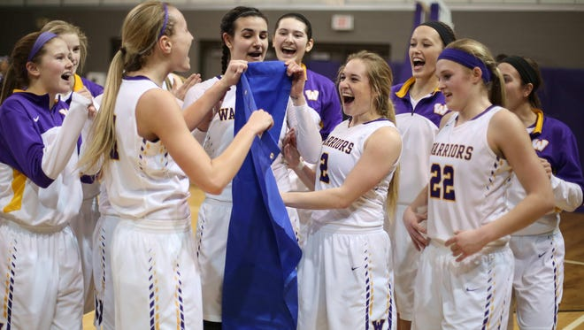 Members of the Waukee girls basketball team celebrate after qualifying for the 2016 Iowa high school girls basketball tournament after an overtime win over Iowa City West on Tuesday, Feb. 23, 2016, at Waukee High School.
