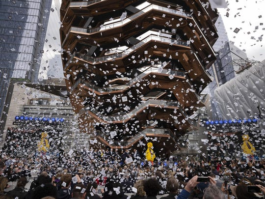 """Confetti swirls around """"Vessel"""" on its opening day at Hudson Yards, Friday, March 15, 2019, in New York. When fully complete, the 28-acre site will include 16 towers of homes and offices, a hotel, a school, the highest outdoor observation deck in the Western Hemisphere, a performing arts center, Vessel and a shopping mall."""