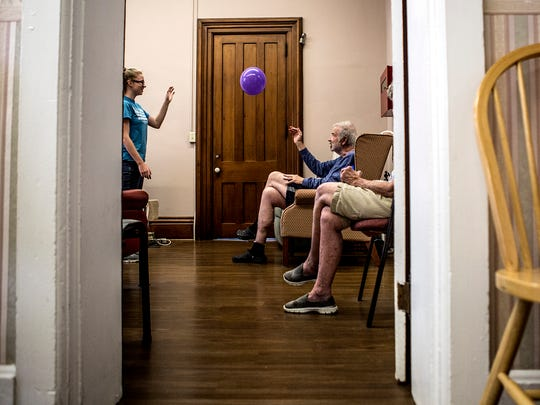 Alyson Camelin, 17, a summer intern at the Carol Strawn Center, tosses a balloon around with Tom Engeman and other clients before beginning their daily exercise routine. Tom is dropped off everyday at the Carol Strawn Center, which offers adult daycare specifically for clients with Alzheimer's and Dementia.