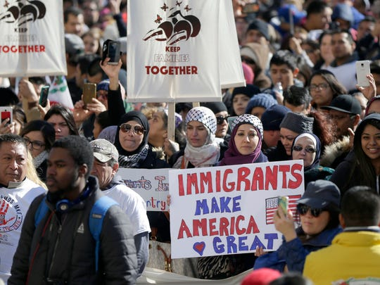 """Protesters hold an """"Immigrants make America Great"""""""