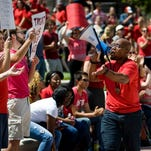 """Jonathan Butler uses a megaphone Aug. 26, 2015, to encourage others to stand and chant during a """"day of action"""" celebrating graduate students and draw attention to their demands in Traditions Plaza on the University of Missouri campus in Columbia, Mo."""