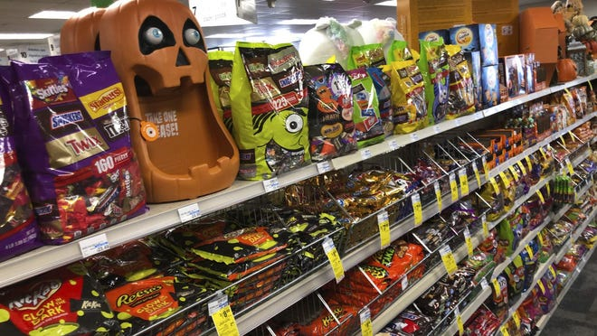Halloween candy and decorations are displayed at a store.
