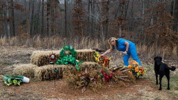 Heather Melton adjusts a flower arrangement at the