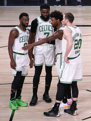 The Boston Celtics' Marcus Smart, second from right, talks with teammates Kemba Walker, left, Jaylen Brown (7) and Gordon Hayward (20) during the first half of Sunday's Eastern Conference final playoff game against the Miami Heat in Lake Buena Vista, Fla. All four players are expected to return for the 2020-21 season, provided Hayward doesn't opt out of the final year of his four-year contract.