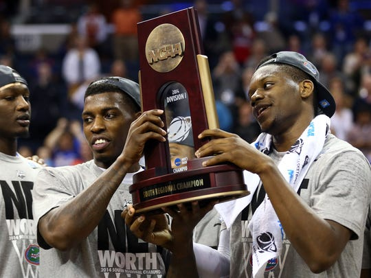 Casey Prather #24 and Will Yeguete #15 of the Florida Gators celebrate with the trophy after defeating the Dayton Flyers 62-52 in the south regional final of the 2014 NCAA Men's Basketball Tournament at the FedExForum on March 29, 2014 in Memphis, Tennessee.