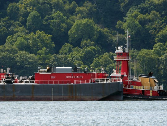 A barge is parked in the Hudson River across from the