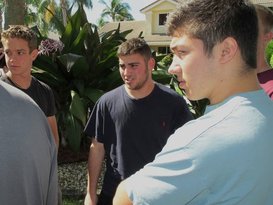 "In this Thursday, Feb. 15, 2018 photo, Jonathan Blank, center, 16, talks with his friends outside his home in Parkland, Fla. Blank and his friends are juniors at Marjory Stoneman Douglas High School, where a shooter killed more than a dozen people on Wednesday. Four people were killed in Blank's classroom by the gunfire, and he was able to escape after police cleared his classroom. ""I've never heard anything that loud, ever,"" Jonathan said of the gunshots. (AP Photo/ Jason Dearen)"