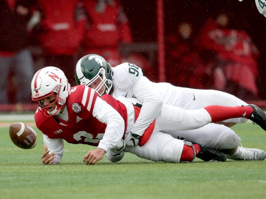 Nebraska quarterback Adrian Martinez (2) fumbles the ball for a turnover after a tackle by Michigan State defensive end Jacub Panasiuk (96), during the first half of an NCAA college football game in Lincoln, Neb., Saturday, Nov. 17, 2018. (AP Photo/Nati Harnik)
