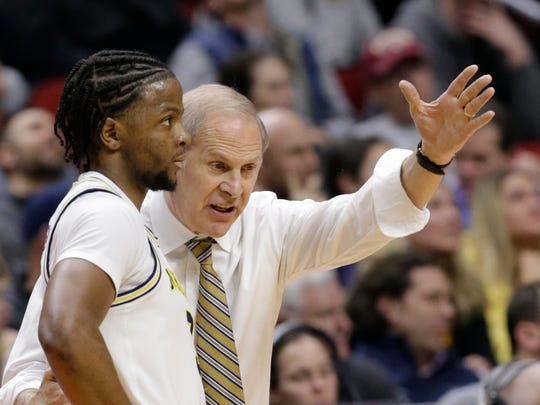 Michigan coach John Beilein, right, talks to Zavier Simpson, left,during the first half of a first round men's college basketball game against Montana in the NCAA Tournament in Des Moines, Iowa, Thursday, March 21, 2019. (AP Photo/Nati Harnik)