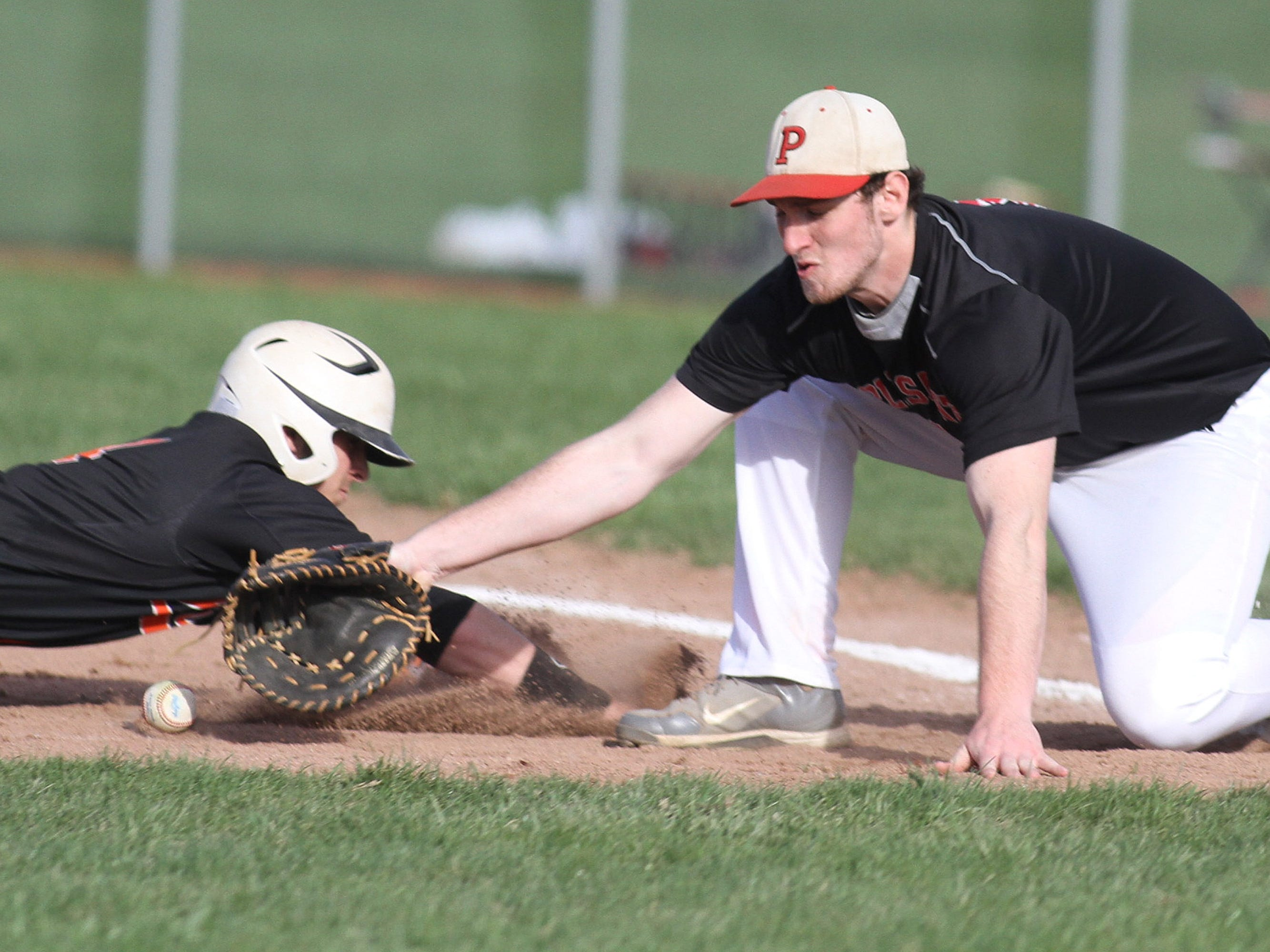 Spartan first baseman Tyler Axline just misses nabbing Tim Davids during a wild Mid Ohio Athletic Conference showdown against North Union.