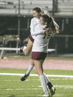 Caroline Morton (15) gives a big hug to Kate David after David scored STM's second goal giving the Cougars a 2-0 halftime lead on Friday night in a semifinal game.