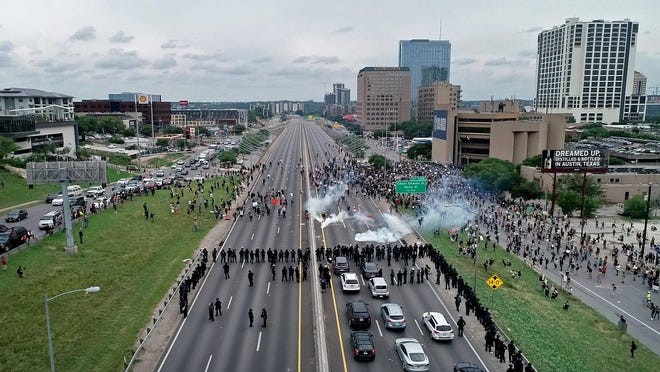 Police clear away protesters who blocked Interstate 35 near the Austin Police Department Headquarters on Sunday May 31, 2020. Protesters continued to demonstrate against the death of George Floyd while in custody of the Minneapolis police.