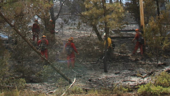Firefighters work fire lines on the Timberon Fire that