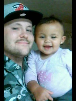 Nathan Dasher sits with his daughter Zandaya. Dasher was killed June 24.