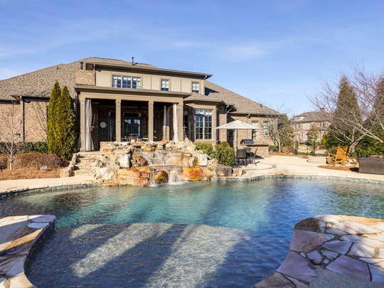 This home, currently listed for sale in Brentwood, has an outdoor living space complete with covered back porch patio with fireplace, and in-ground pool with hot tub and waterfall.