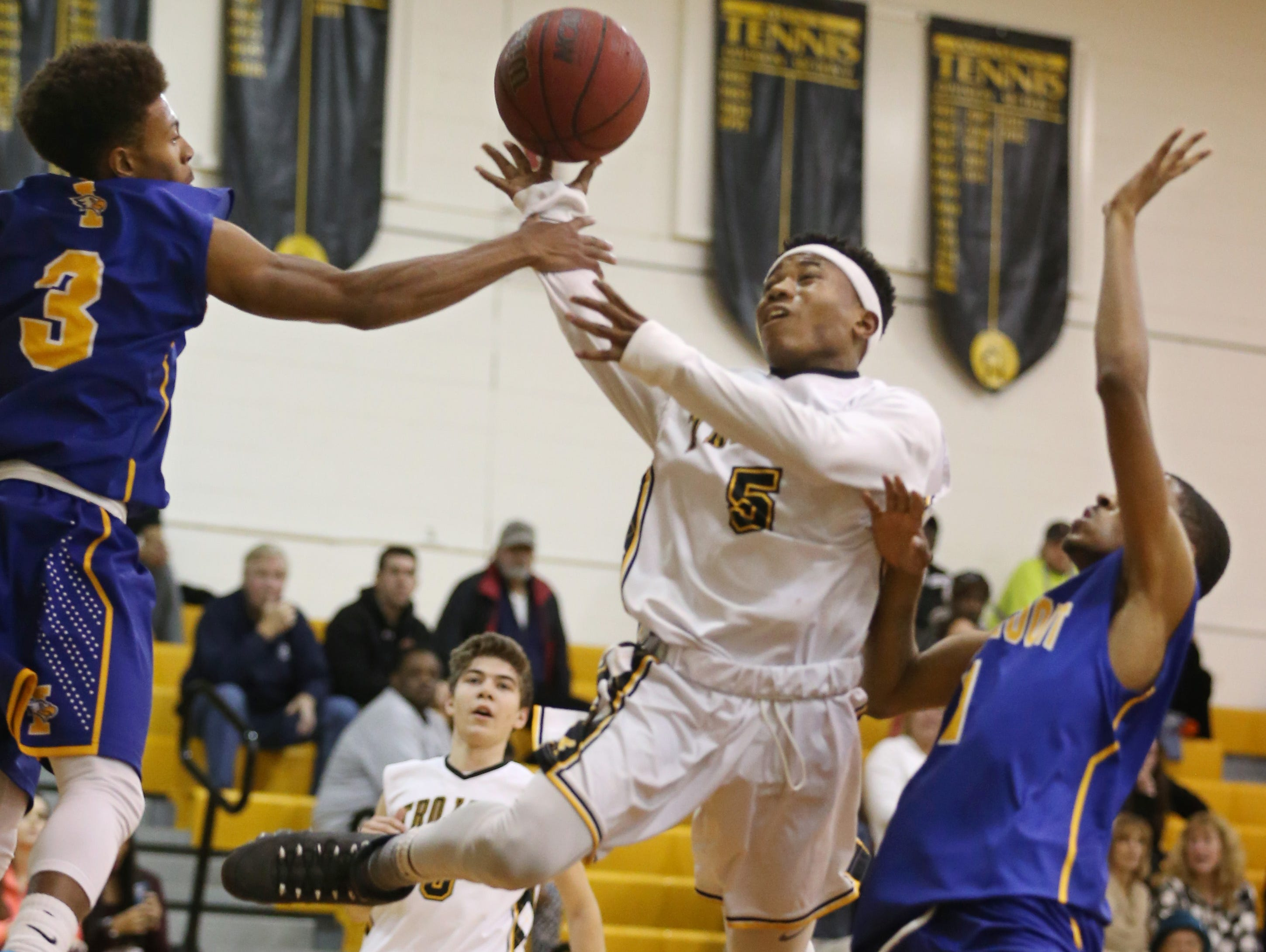 Greece Athena's Kenny Speed, center, draws a foul from Irondequoit's Ty'Reek Sizer, left, as he drives the lane in the first half during their game Monday, Dec. 14, 2015 at Greece.