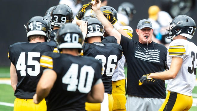 Iowa strength and conditioning coordinator Chris Doyle huddles up with players during a Hawkeyes football Kids Day scrimmage, Saturday, Aug. 10, 2019, at Kinnick Stadium in Iowa City, Iowa.