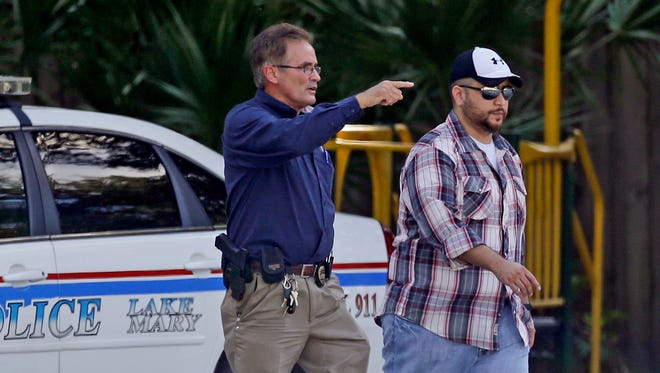 Geroge Zimmerman, far right, is escorted to a home by a Lake Mary police officer, center, and Shawn Vincent, an assistant to his attorney, on Sept. 9, 2013, in Lake Mary, Fla., after a domestic incident in the neighborhood where Zimmerman and his wife, Shellie, had lived during his murder trial.