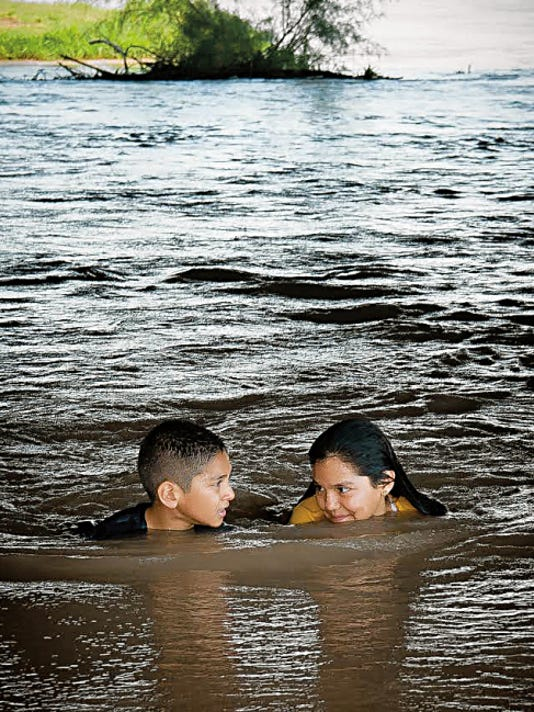 Ryan Martinez, 8, and his 10-year-old sister Arlette Martinez cool down in the Rio Grande by La Llorona Park on Wednesday. Water will continue to flow in the Rio Grande channel through the end of September.