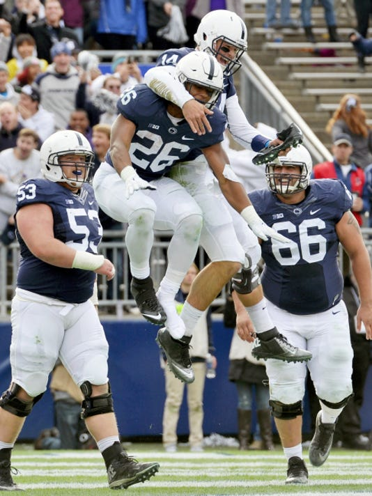 Penn State Nittany Lions running back Saquon Barkley (26) leaps over Illinois Fighting Illini defensive back V'Angelo Bentley (2) on his way to a touchdown as Penn State beat Illinois 39-0 at Beaver Stadium on Saturday, October 31, 2015.