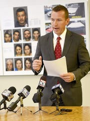 Lebanon District Attorney David Arnold speaks during a press conference Wednesday afternoon to announce a major drug bust. Behind him are photos of 11 suspects who were arrested. The drug ring is accused of selling an estimated 2.5 million of drug since March last year.